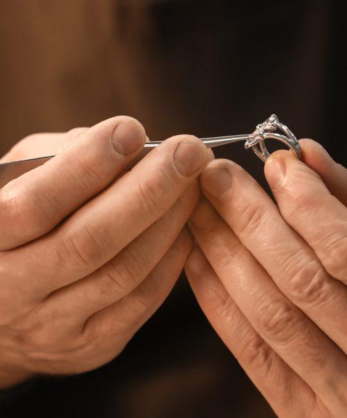 Jeweler repairing ring with gem, closeup